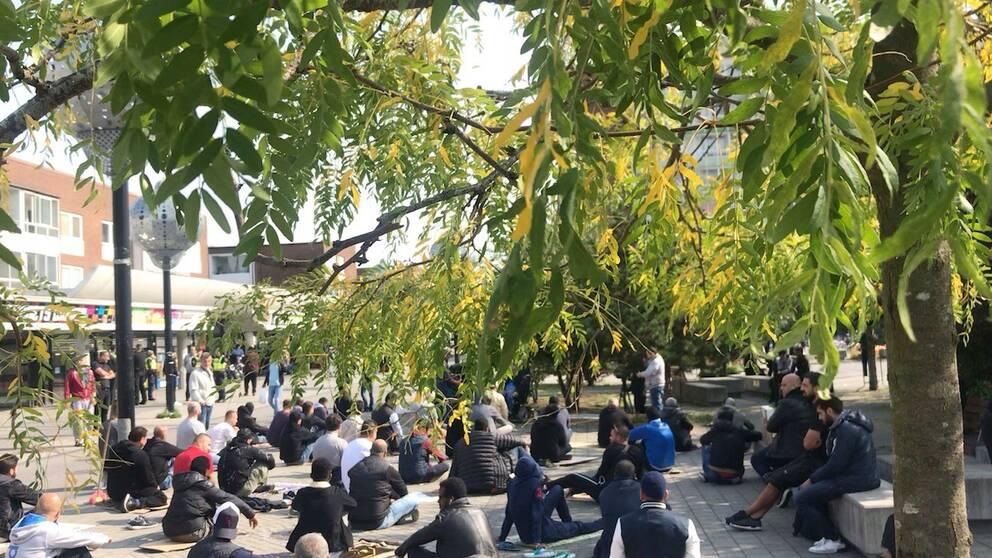 Ett 30-tal män har vid lunchtid samlats för fredagsbön nära den plats där en koran brändes på fredagsmorgonen.