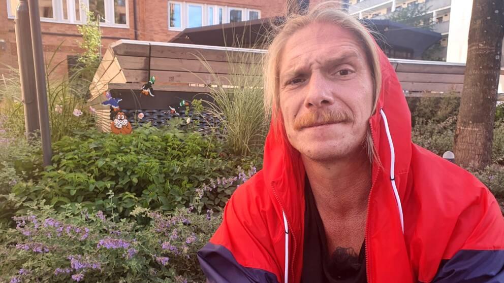 Konstnären Johan Karlgren sitter med rödblå jacka, med huvan över huvudet. Bakom honom syns en rabatt där ett av hans verk, en hund och några ankor, gömmer sig.