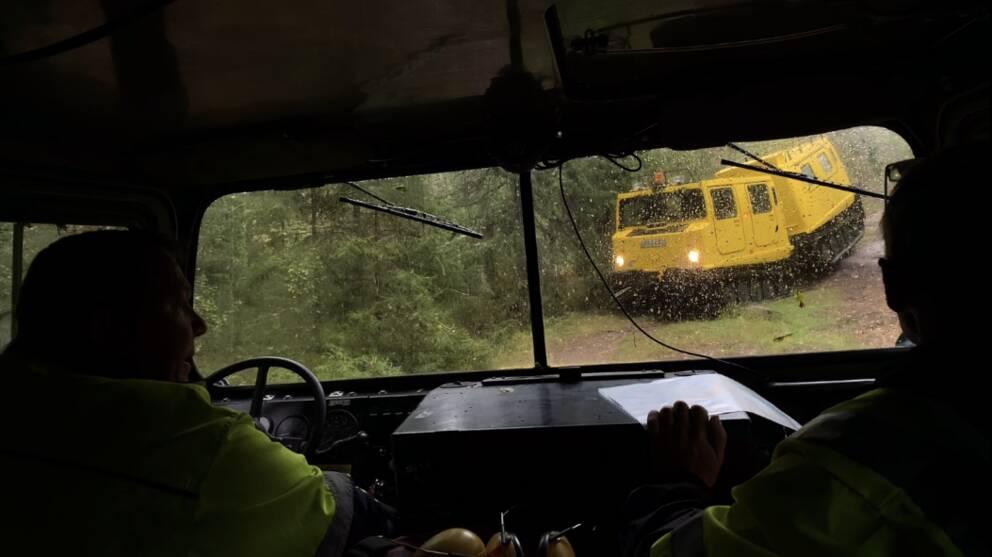 Sikt ut från en bandvagn som möter en likadan gul bandvagn på en skogsstig.