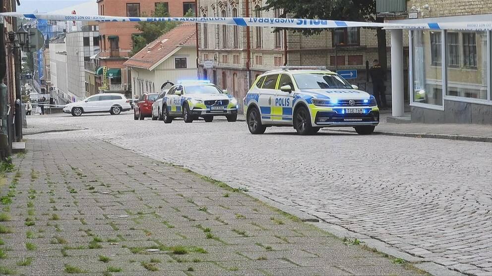 Två polisbilar med blåljus parkerade på en gata i Borås.