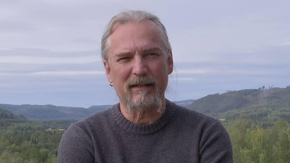Bild på gråhårig man i hästsvans med skägg, ring i höger öra. I bakgrunden ett bergslandskap.