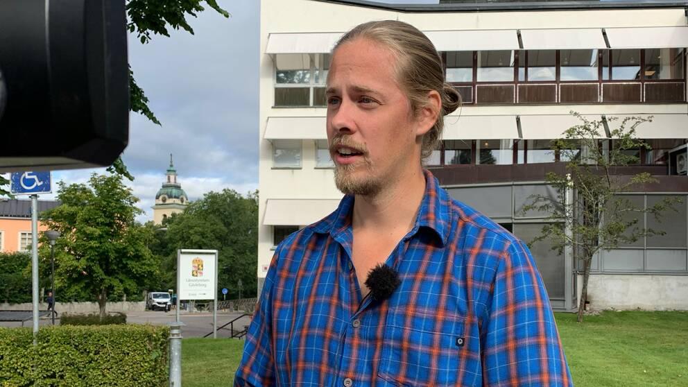 Peter Nordling intervjuas utomhus, håret uppsatt och iklädd en blå och röd skjorta.