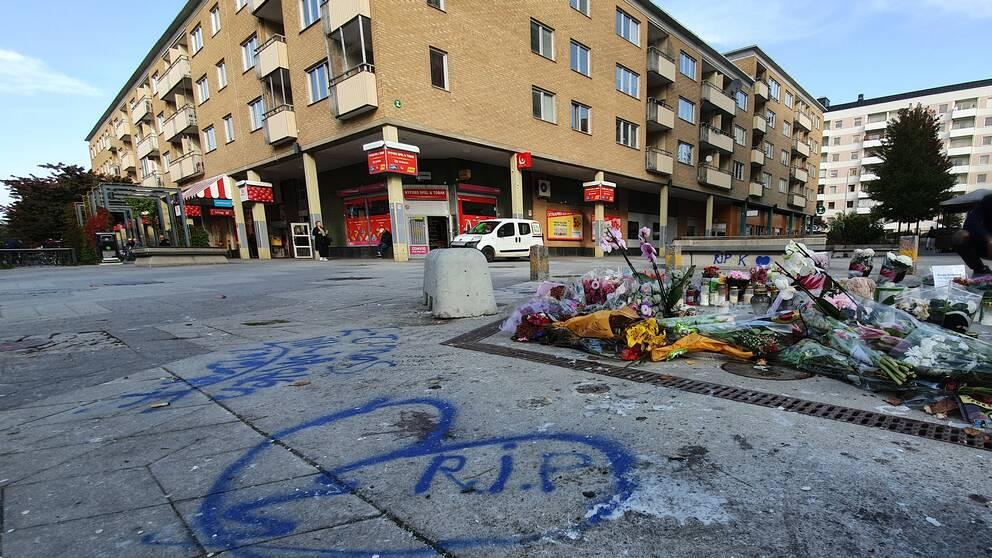 Blommor och hälsningar till den skjutne pojken syns i Nyfors i Eskilstuna.