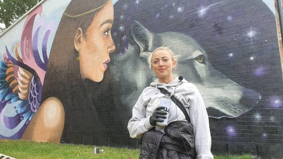 Konstnären Frida Stiil Vium framför hennes väggmålning i Åtvidaberg