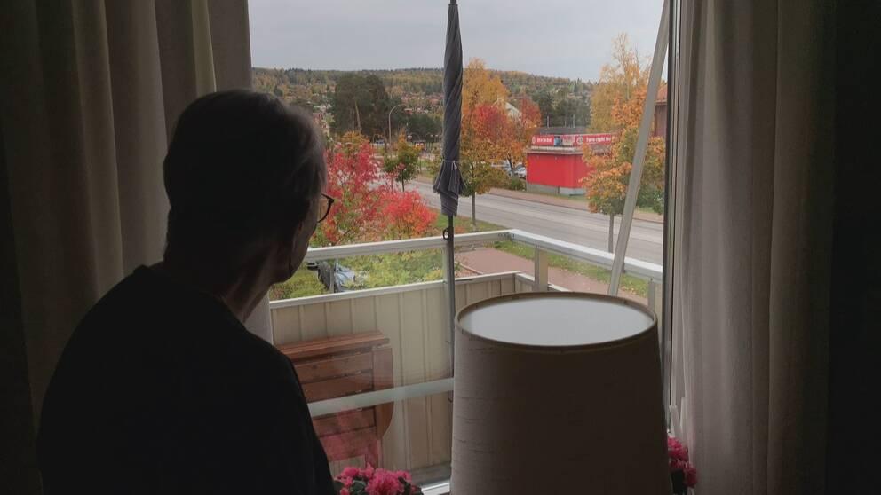 en äldre dam står med ryggen mot kameran och tittar ut mot en väg i Rättvik