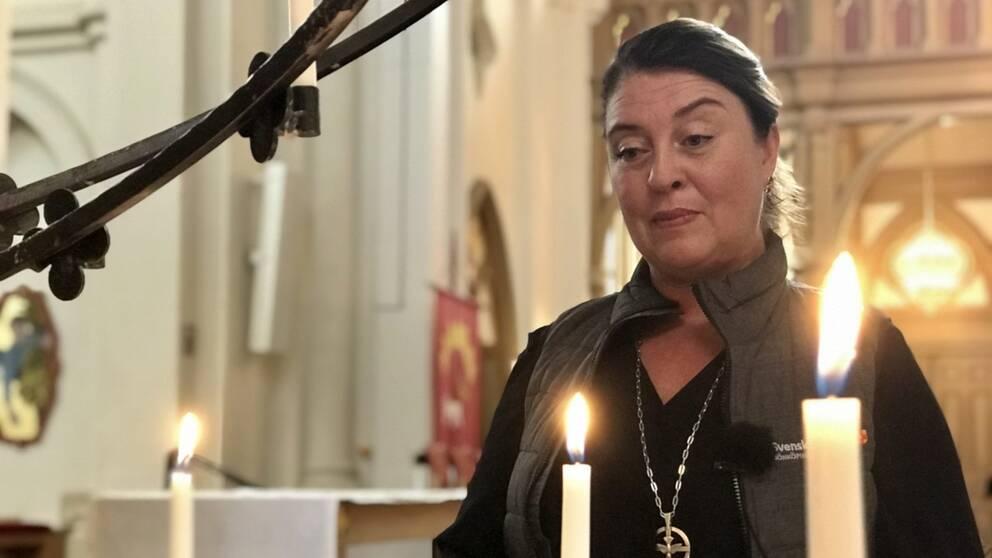 Linda Wennerholm, diakon i Svenska kyrkan i Jönköping står i en kyrka med levande ljus i förgrunden.