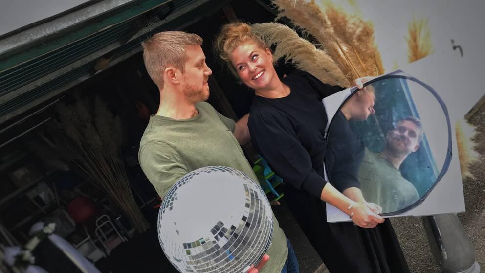 Karin Sandbergs och Alfred Andersson står framför garaget med diverse bröllopsdekorationer så som discokula och spegel och pampagräsvippor.