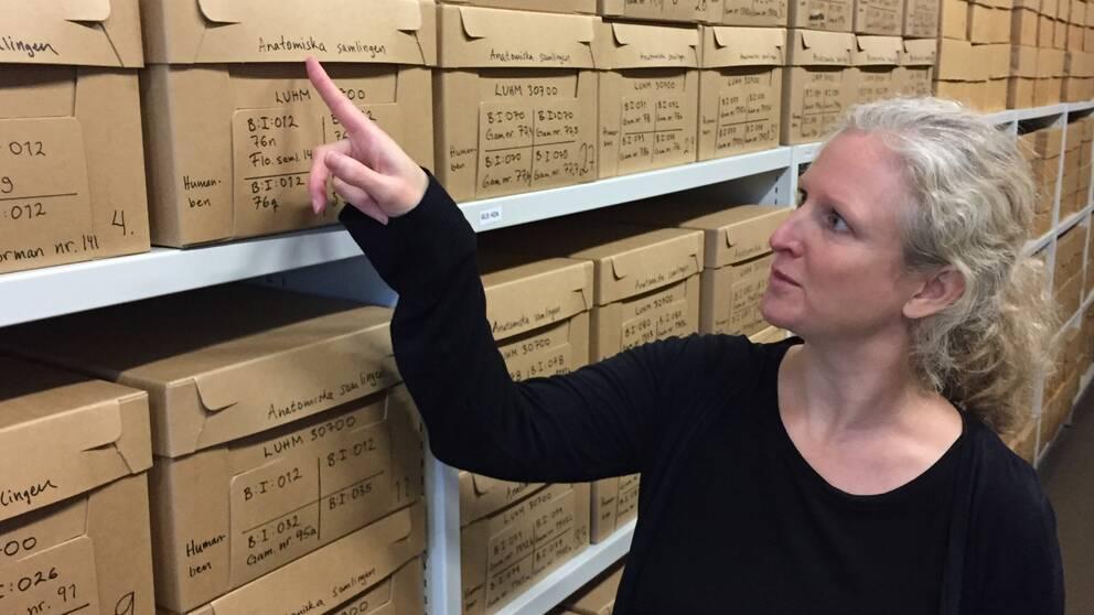"""Jenny Bergman, antikvarie på Historiska museet vid Lunds universitet står i museets magasin och pekar mot en av lådorna med titeln """"Anatomiska samlingen"""" som innehåller samiska kvarlevor."""