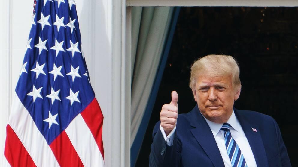 Donald Trump ger tummen upp från balkongen på Vita huset under sitt framträdande under lördagen.