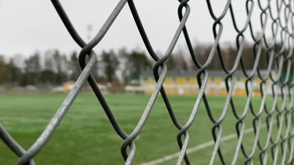 En fotbollsplan fotat genom ett stängsel.