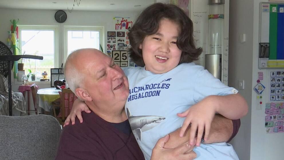 En pappa sitter med sitt barn i knät, i en soffa, båda ler.