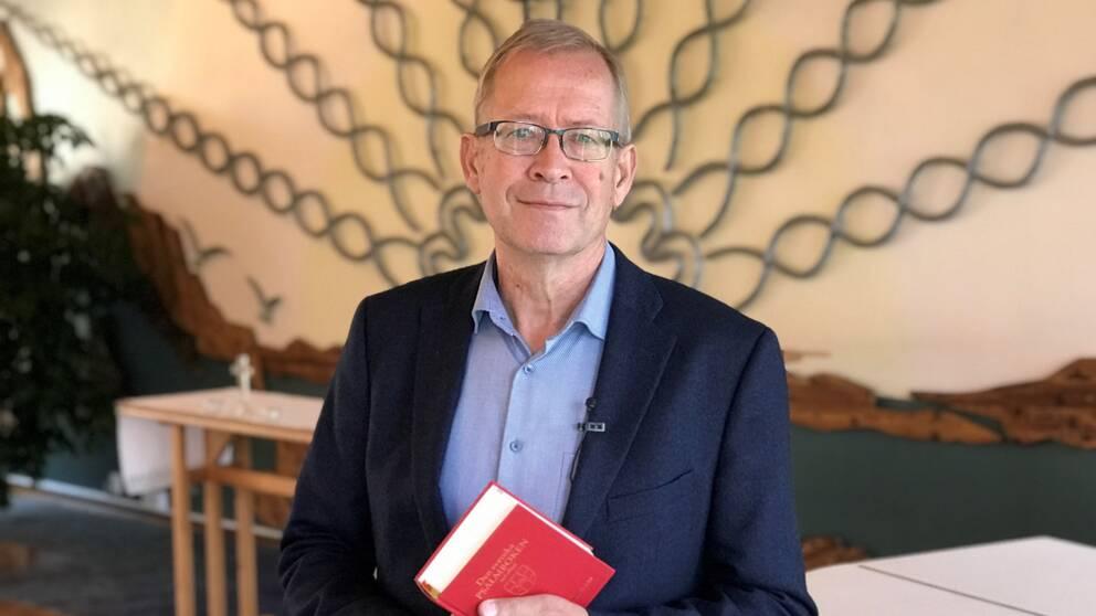 Henrik Tobin med psalmbok i händerna