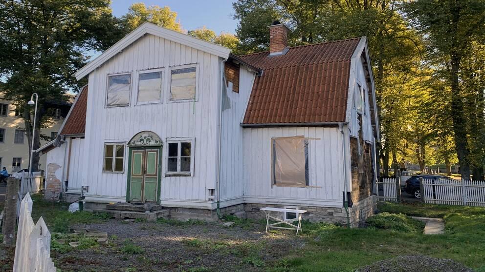 Stor vit villa med igenbommade fönster och sliten fasad.
