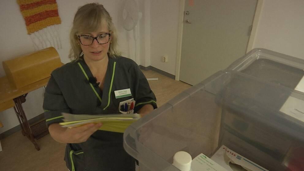 Sjuksköterskan Malin håller i en mapp med instruktioner och står intill en låda med skyddsutrustning.