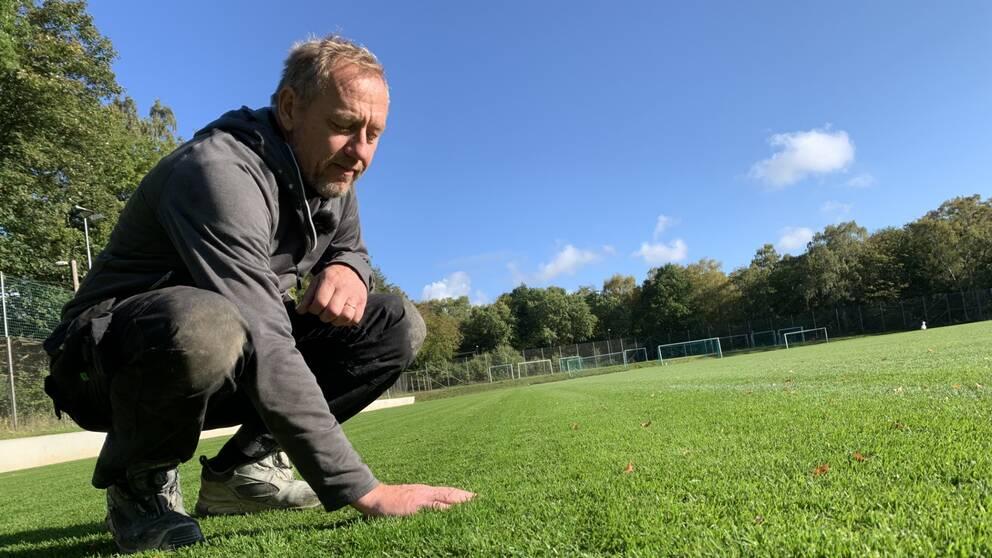 Anders Mårtensson sitter på huk och känner på gräset med sin hand