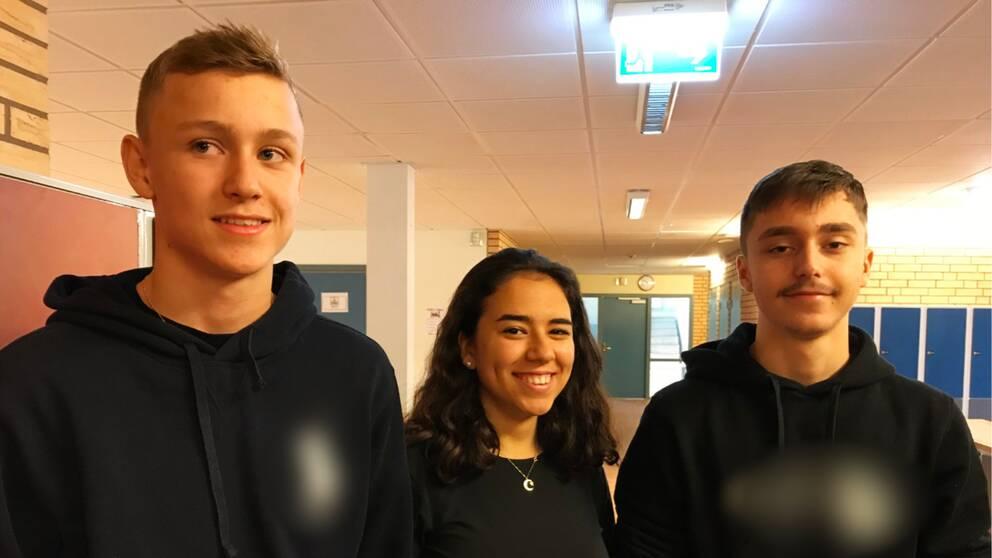Tre skolelever Adam Adler, Leila Yigit och Edin Music står i skolkorridor.
