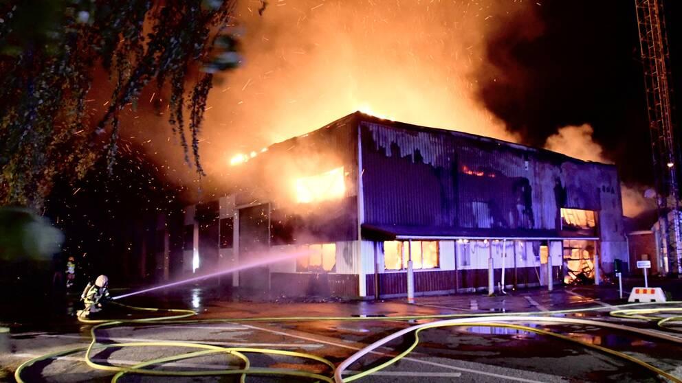 Ett fyrkantigt hus som brinner och en person står på knä med en brandslang som sprutar vatten.