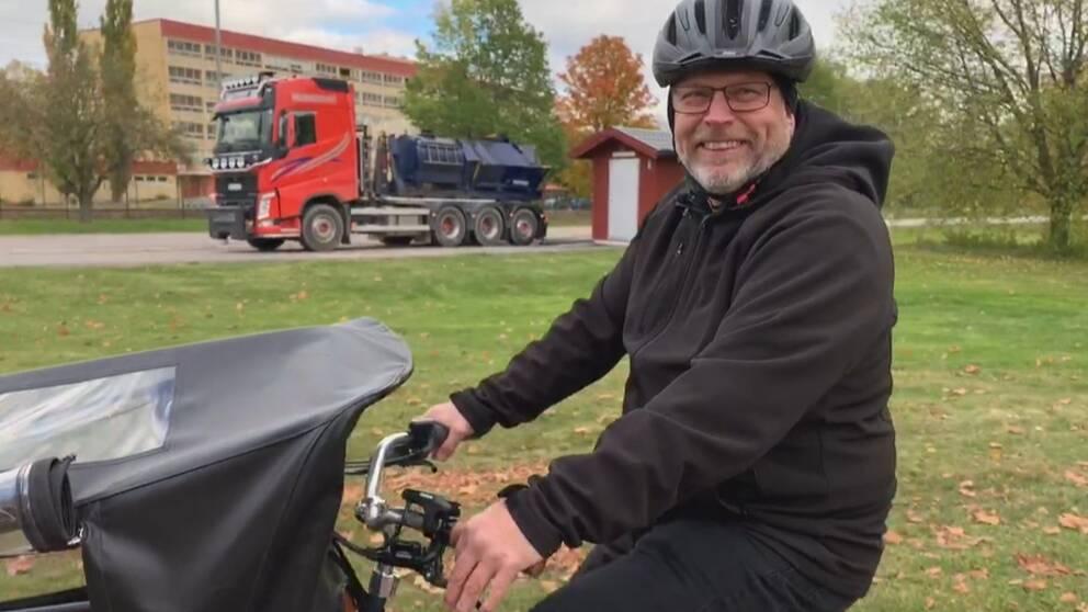 en äldre man med cykelhjälm cyklar på en elcykel. en långtradare i bakgrunden.
