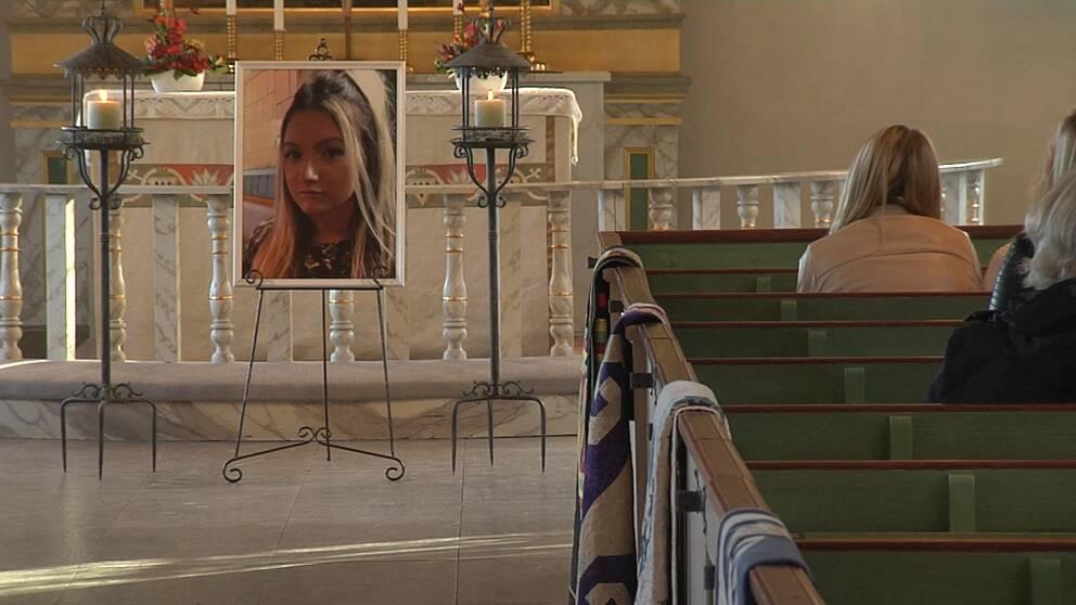 En stor bild på en blond flicka, längst fram i en kyrksal med gröna kyrkbänkar.