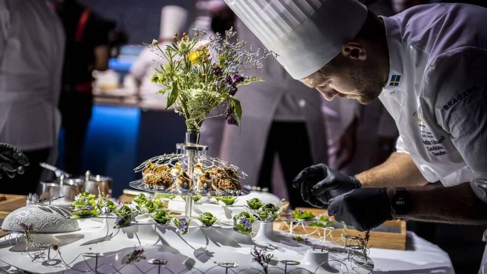 kocken Sebastian Gibrand iklädd kockhatt dekorerar mat.