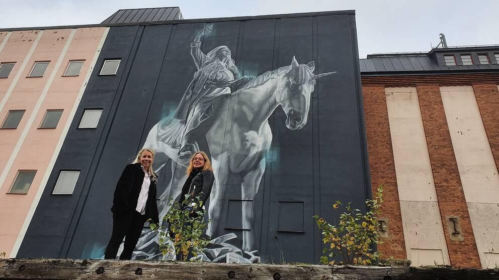 Kristin Kellander (L), ordf kultur- och fritidsnämnden Mjölby samt Lena Lindgren kultur- och fritidsstrateg i samma kommun framför den nya stora väggmålningen av Judith de Leeuw från Nederländerna.