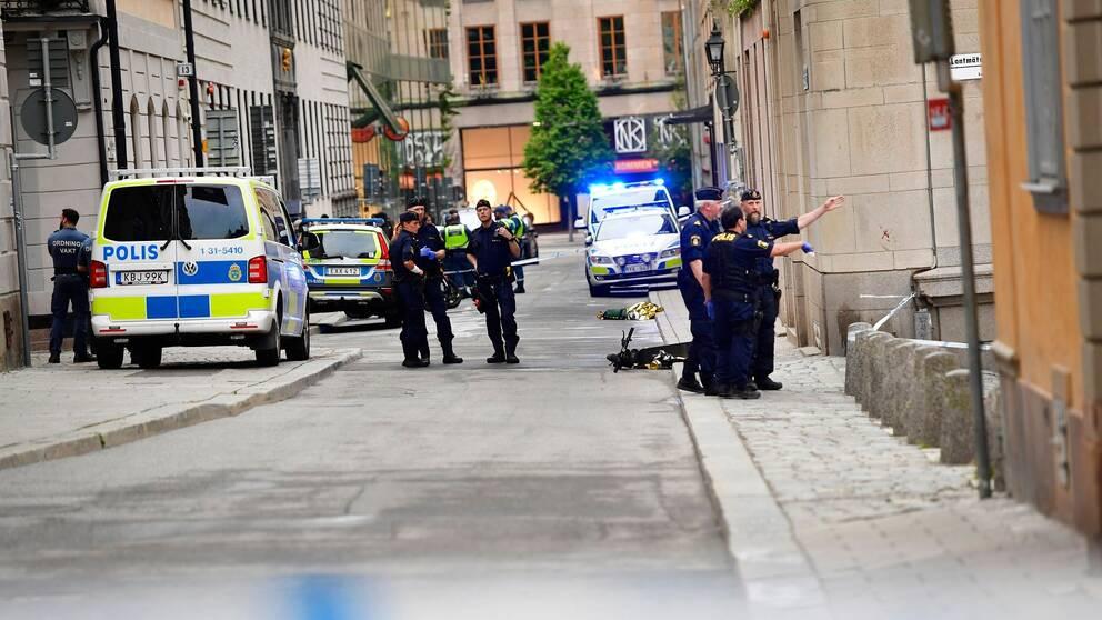 Flera polisbilar står parkerad längs en gata i Stockolms city och grupper av poliser pratar med varandra.