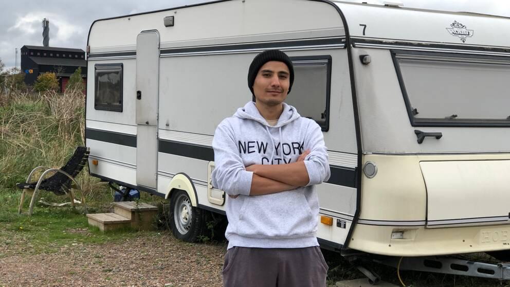 Salman Yosofi står framför den vita husvagn han bor i utanför Staffanstorp.