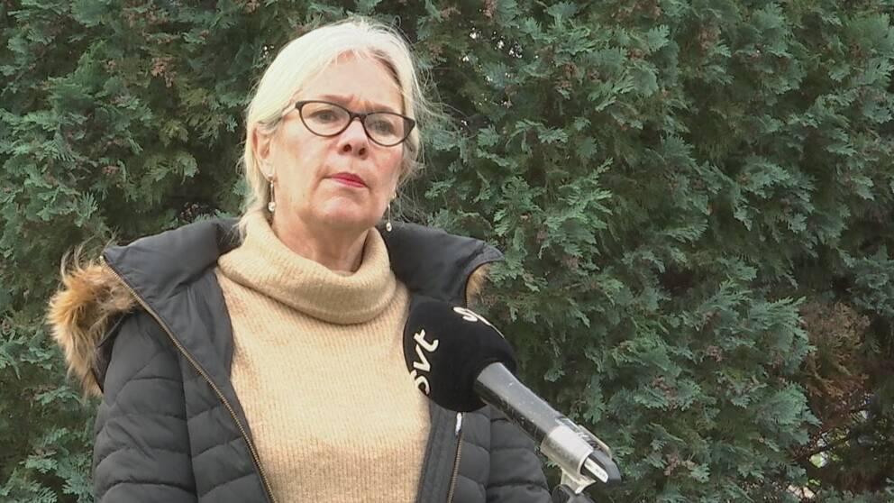 Kvinna i glasögon och tjock vinterjacka står framför en häck och pratar i en SVT-mikronfon