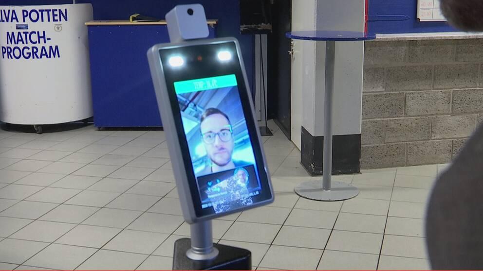 Bild på en febermätare med skärmen i fokus. På skärmen syns en man i 30-årsåldern som testar febermätaren. Det är bara hans ansikte som syns.