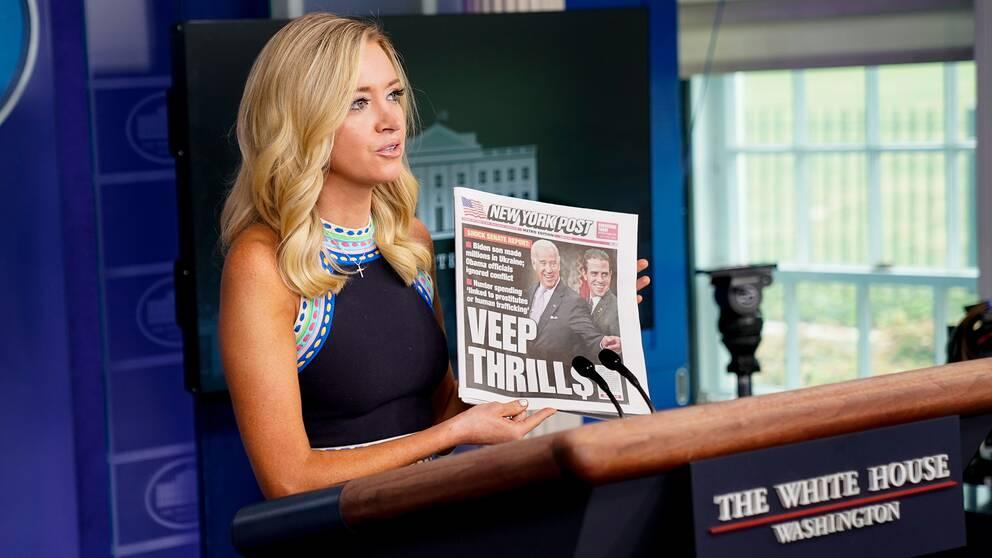 Kayleigh McEnany står bakom en talarstol och håller upp ett ex av New York Post under en presskonferens.