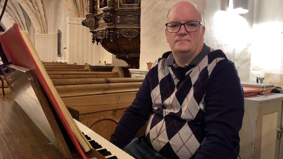 man i stickad tröja sittandes vid orgel