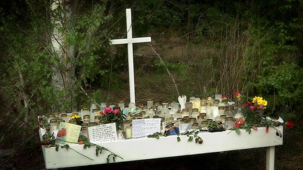 Ett vitt kors bakom ett bord fullt med ljus och blommor