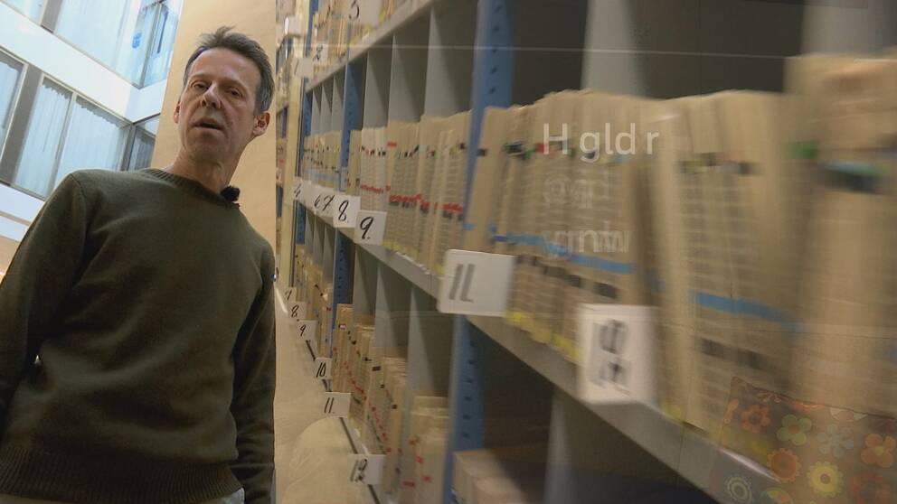 Magnus Nord står i en trapp, bredvid ser man journaler i ett arkivskåp och bokstäver som syns lite halvt.