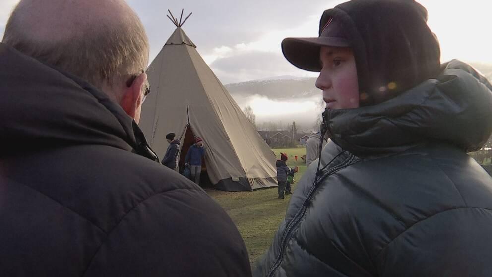 Bild på två män som står framför en tältkåta