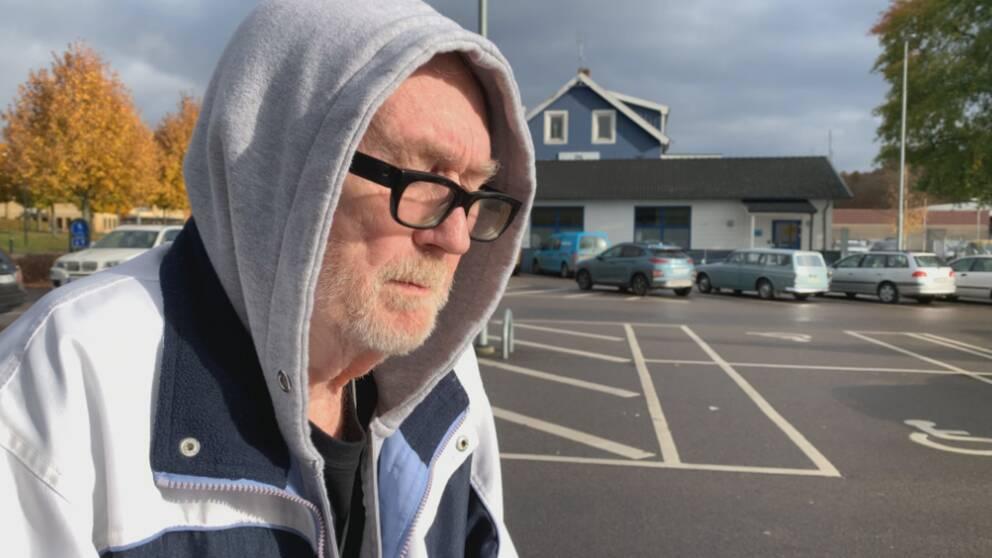 En äldre man står på en parkering och tittar ned mot marken.