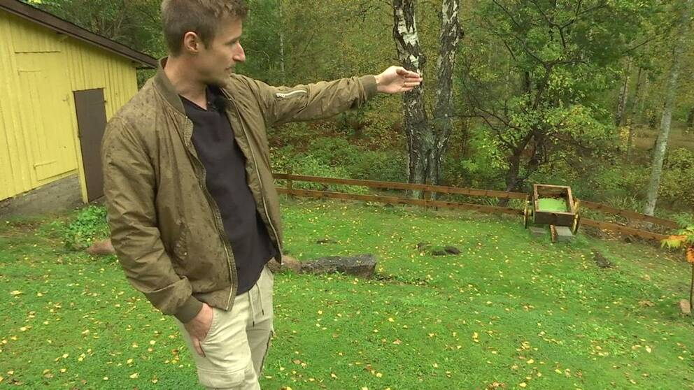 Viktor Backman står i sin trädgård och pekar bortåt.