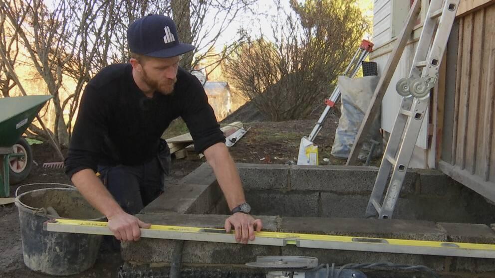 Man i keps och svart tröja mäter med ett vattenpass på en utbyggnadsgrund