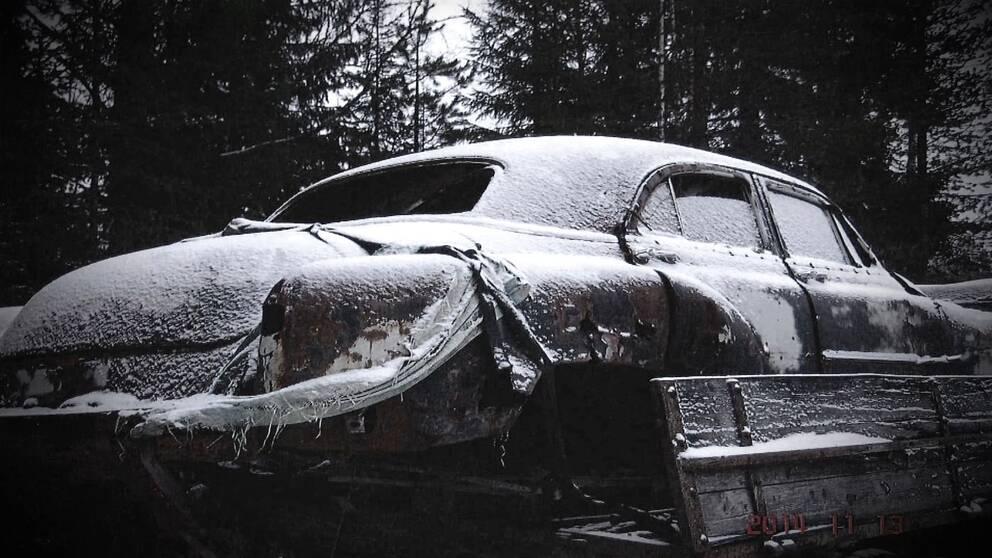 svartvit bild på en gammal bil. lätt översnöad.