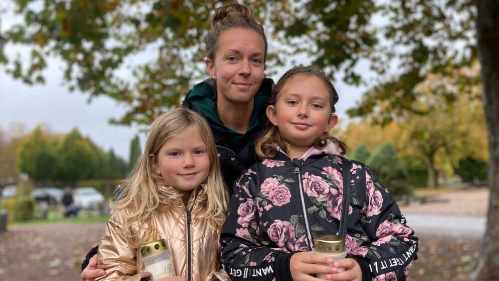 Sofie, Nelia och Novalie Gustavsson tänder ett ljus för barnens farfar på alla helgons dag.