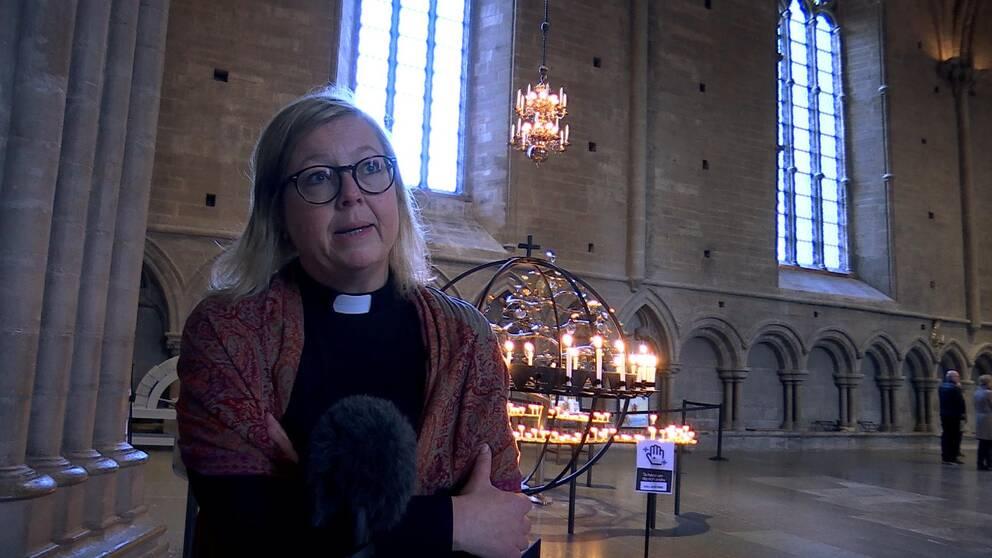 Helen står i prästkläder framför en ring av ljus i domkyrkan.