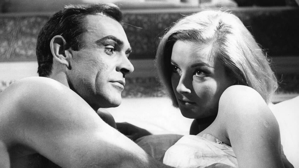 Svartvit bild där Sean Connery och skådespelerskan Daniela Bianchi ligger i bara överkroppar under ett täcke.