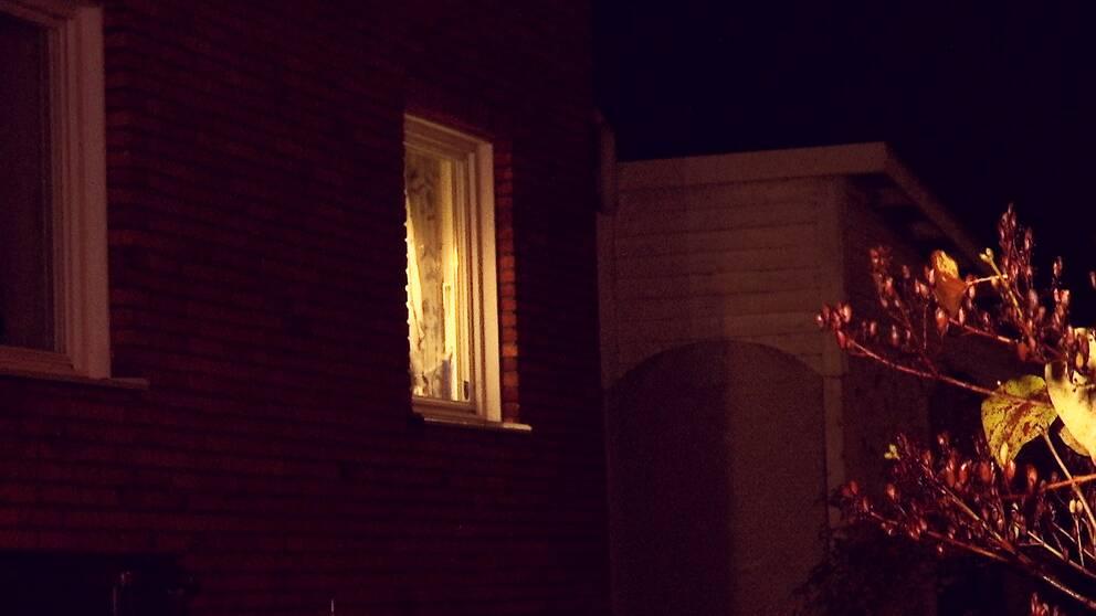 Ett tegelhus i mörker med ett fönster som det lyser i.