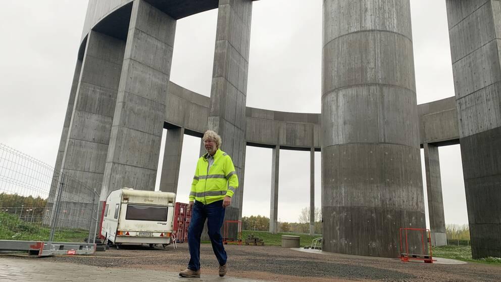En man promenerar framför ett vattentorn