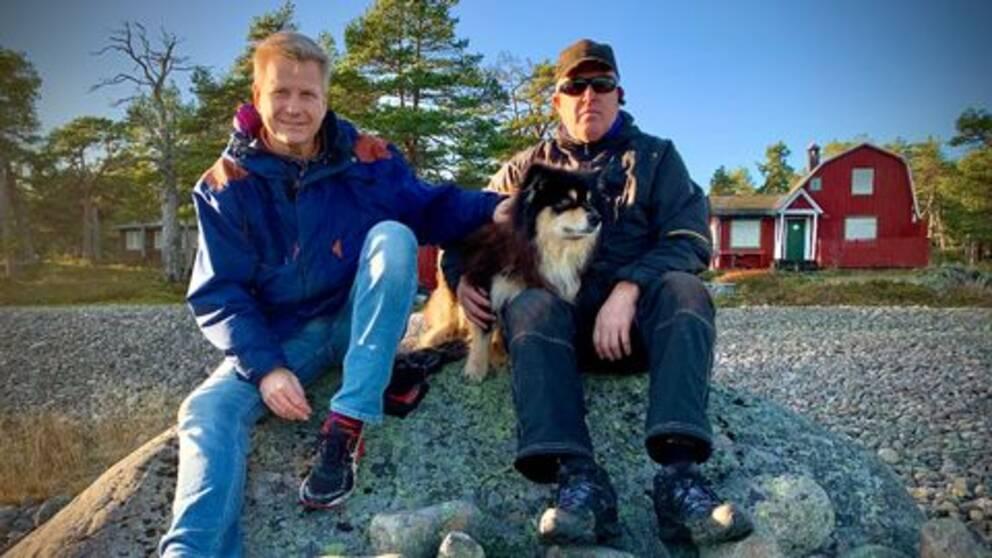 Göran Gabrielsson och Ove Olsson – två män med en hund sitter på sten i skärgården, sommarhus i bakgrund