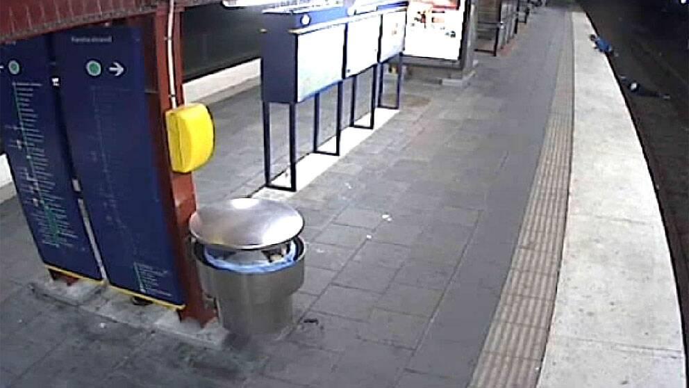 I stället för att hjälpa en man som låg medvetslös på tunnelbanespåret i Sandsborg valde en förbipasserande att råna honom på mobil, plånbok och guldkedja och gå därifrån. Foto: SL:s övervakningskamera
