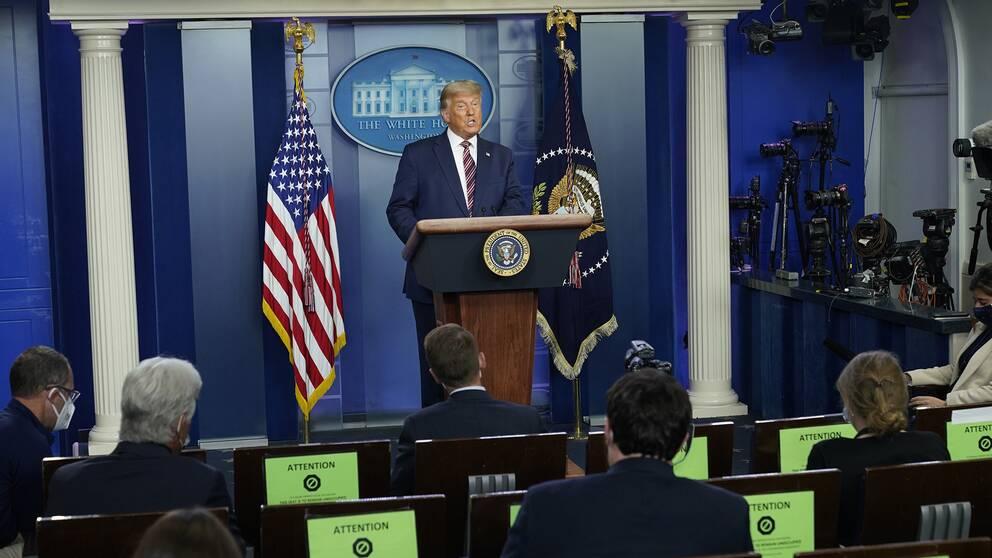 Donald Trump i talarstolen i Vita huset framför pressen.
