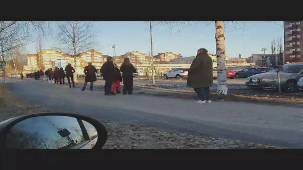 Folk som står i kö under hösten bredvid Piteå busstation