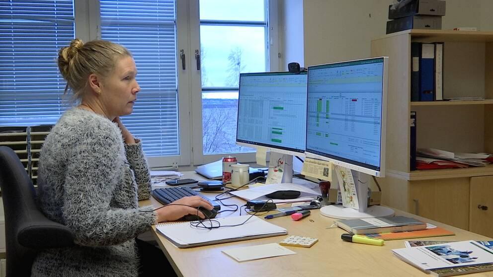 Kvinna med blont uppsatt hår sitter vid ett skrivbord med två dataskärmar.