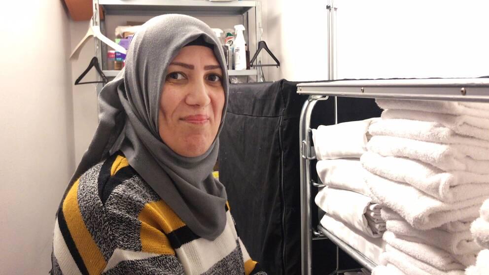 Shamam Hamid står i ett förrådsrum på hotellet. I bakgrunden syns galgar, sprejflaskor med rengöringsmedel och framför henne finns en hylla med handdukar och lakan.
