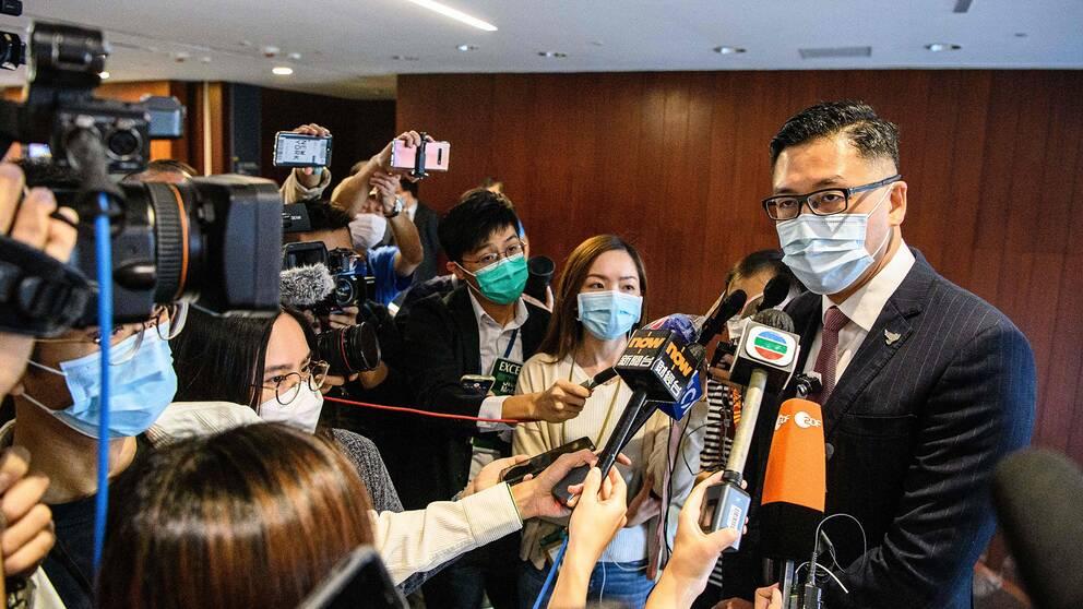 Parlamentsledamoten Lam Cheuk-ting svarar på frågor från reportrar med mikrofoner i inomhusmiljö, alla införda munskydd.